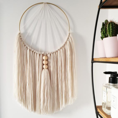 Photo of Cream macrame wall hanging – Home accessory with natural wooden beads and handmade tassel. Featured in Style at Home magazine.
